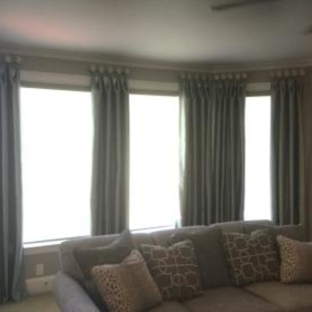 These beautiful light filtering roller shades compliment the stationary drapery panels accented with medallions.