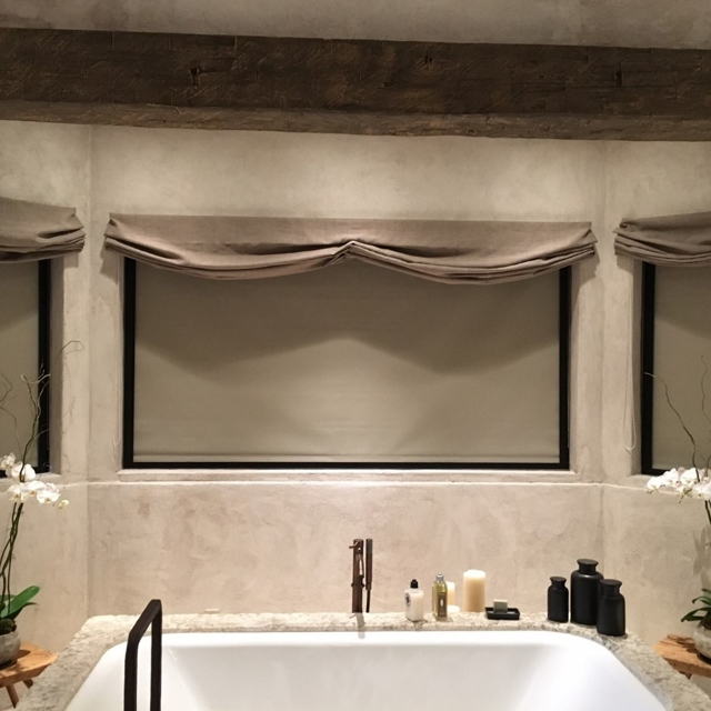 Closed tan shades above bathtub in master bathroom