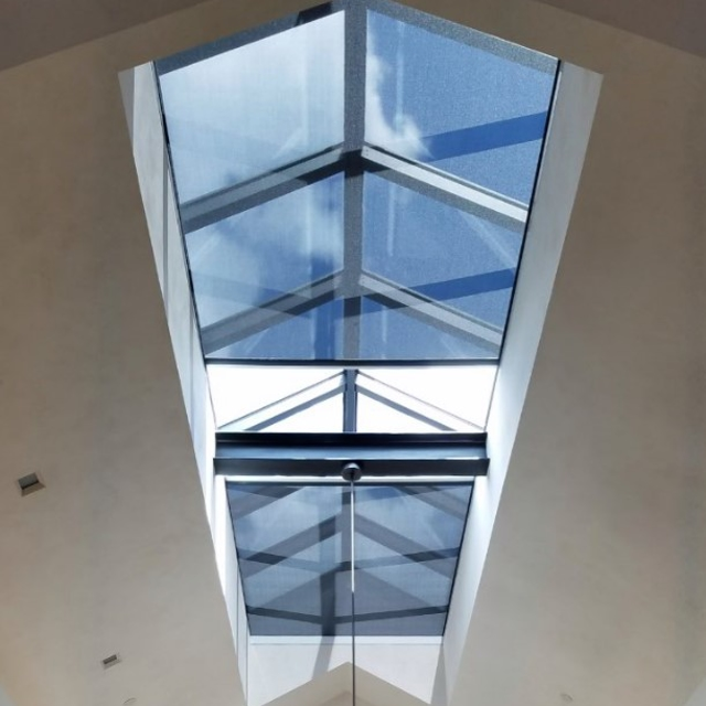 Black motorization shades covering indoor sky light