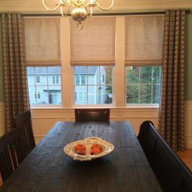 Grommet Drapes compliment the cordless Roman Shades on this large window.