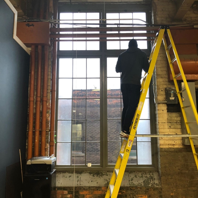 Tall ladders are needed to install motorized roller shades on tall windows at the Cotton Factory in Hamilton