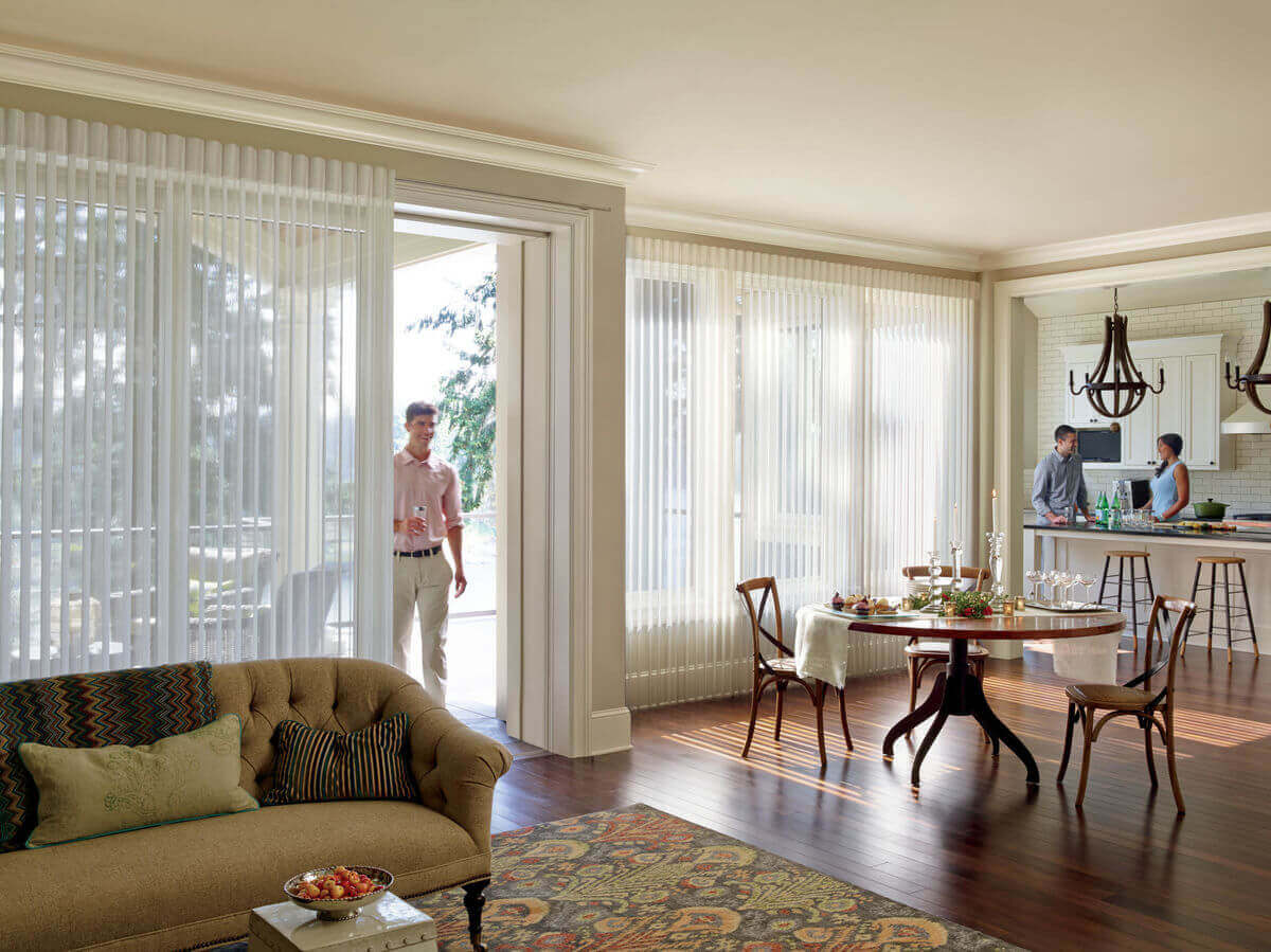 Window treatments designed to operate over sliding glass doors will provide light control and privacy without hindering the use of the doorway.